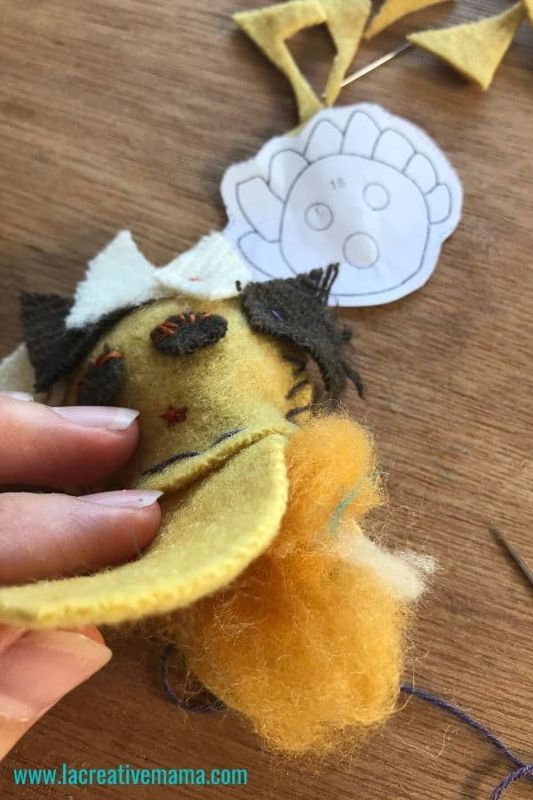making a handmade plushie by cutting fabric and handsewing it