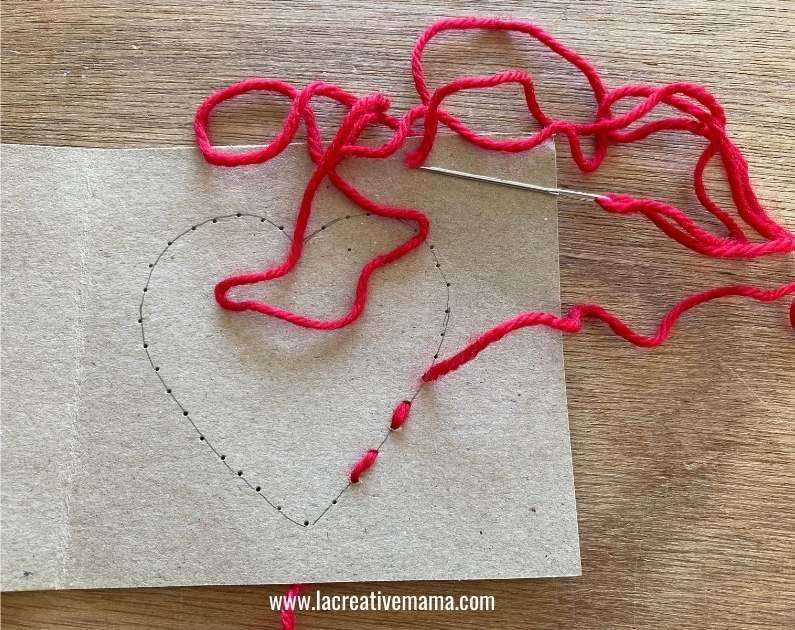 sewing a running stitch on a valentines handmade card