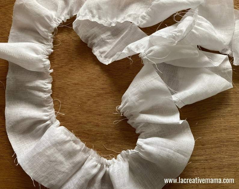 gathering a piece of fabric to make ruffles for a baby pillow tutorial