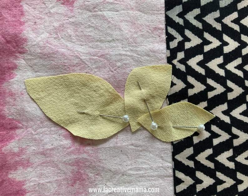 sewing an applique flower in the outside pocket of a tote bag