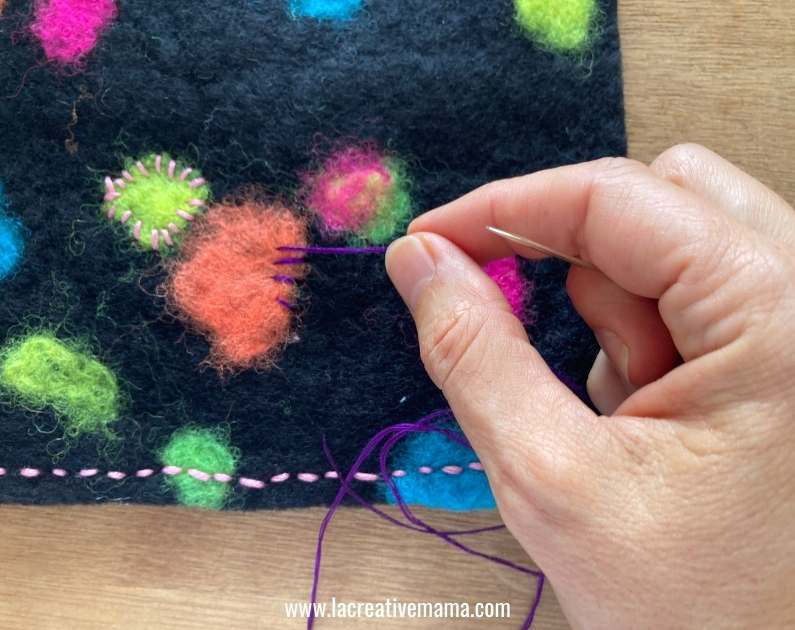 decorating a  piece of felt with embroidery stitches , whipstitch and backstitch